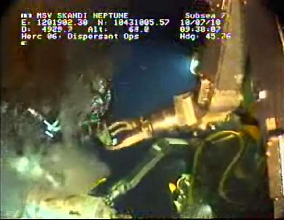 In this image taken from video provided by BP PLC, the arm of a remotely operated vehicle works at the Deepwater Horizon oil spill site in the Gulf of Mexico, Saturday, July 10, 2010. Undersea robots manipulated by engineers a mile above were expected to begin work Saturday removing the containment cap over the gushing well head in the Gulf of Mexico to replace it with a tighter-fitting cap that could funnel all the oil to tankers at the surface. If all goes according to plan, the tandem of the tighter cap and the tankers could keep all the oil from polluting the fragile Gulf as soon as Monday. But it would be only a temporary solution to the catastrophe unleashed by a drilling rig explosion. It won't plug the busted well and it remains uncertain that it will succeed. (AP Photo/BP PLC) NO SALES Photo: AP