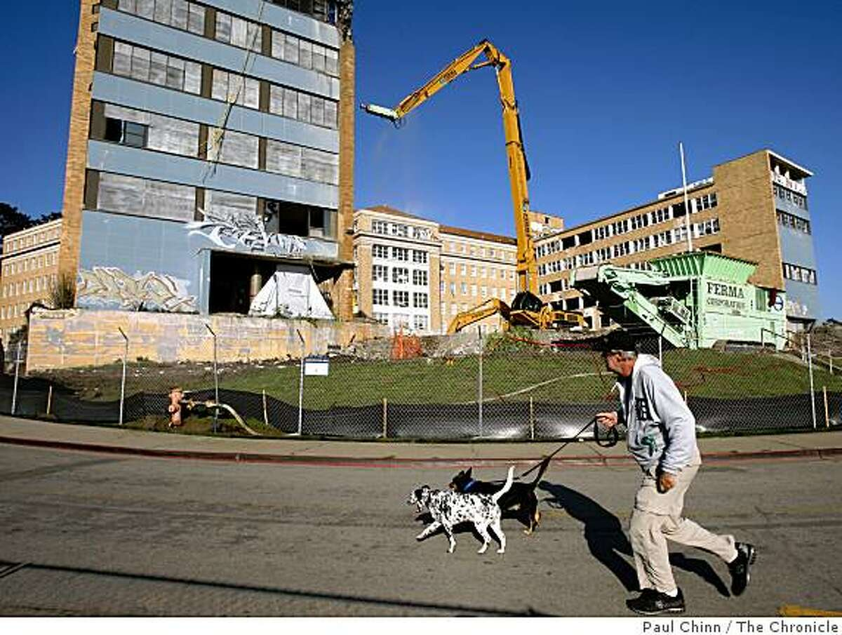 Mick Gast walks with Riley and Pup Pup past the long-abandoned Public Health Service Hospital at the Presidio where crews began demolishing the two wings in San Francisco, Calif., on Thursday, Dec. 4, 2008.
