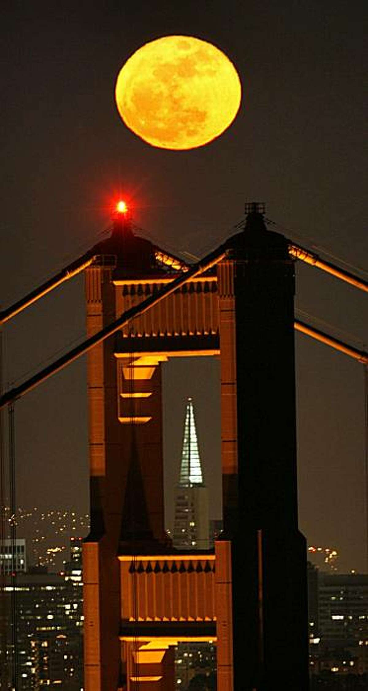 A full moon rose over the Golden Gate Bridge April 20, 2008 as it the bridges north tower framed the Transamerican Pyramid of the city skyline. 4/20/08 Photo by Frederic Larson / San Francisco Chronicle