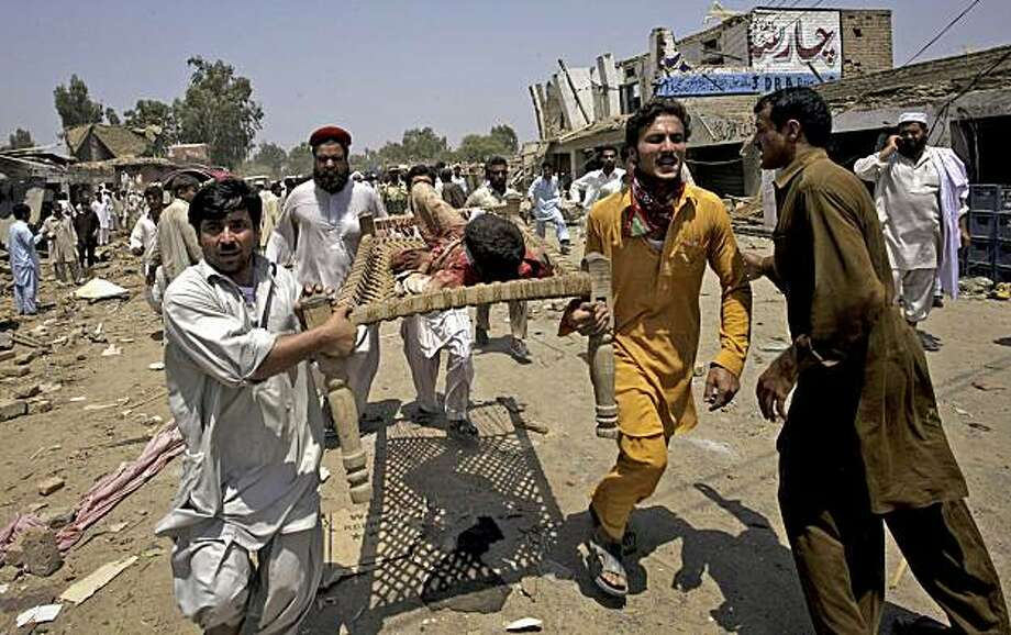 People carry an injured person from the spot of bombing in Yakaghund in Pakistani tribal area of Mohmand on Friday, July 9, 2010. A suicide bomber on a motorcycle struck outside a government office Friday in the region where Pakistan's army has fought theTaliban, killing scores of people and left many injured, officials said. Photo: Mohammad Sajjad, Associated Press