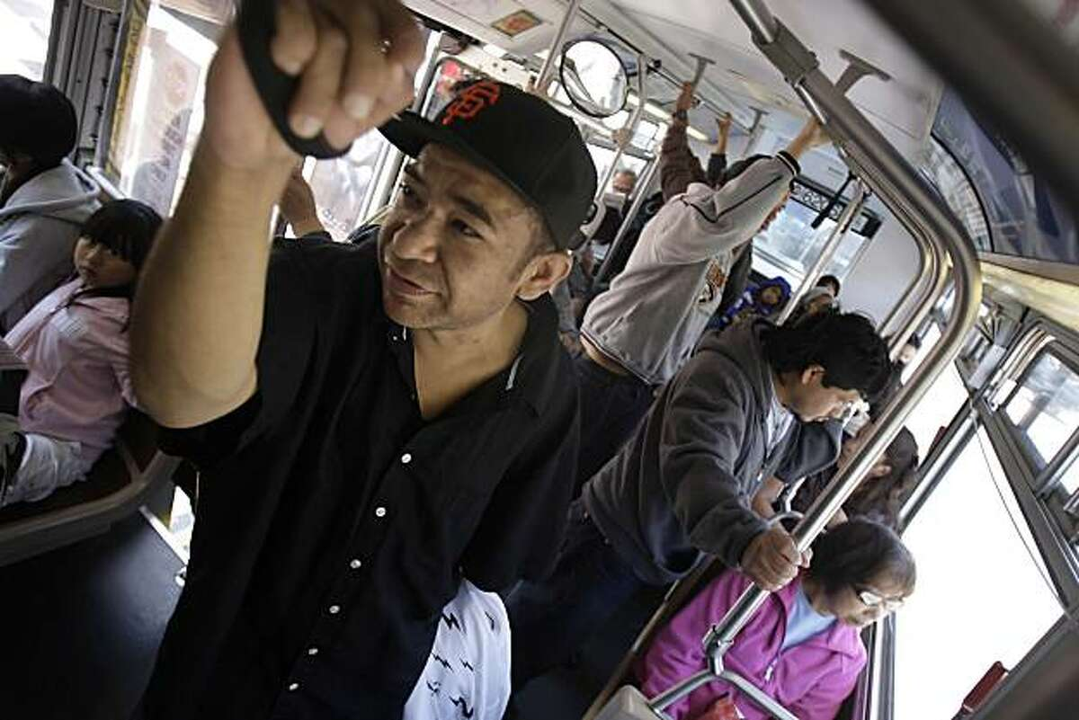 Orlando Cesna of San Francisco holds a hand strap while riding the 14L Muni line in San Francisco, Calif. on Tuesday July 6, 2010.