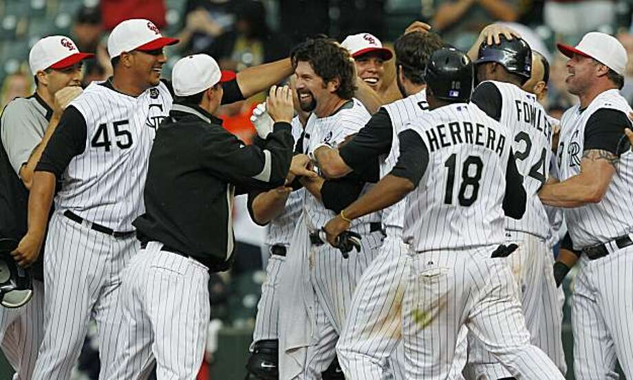 Colorado Rockies' Todd Helton, center, is congratulated by teammates after hitting a sacrifice fly to drive in the winning run against the San Francisco Giants in the 15th inning of the Rockies' 4-3 victory in a baseball game in Denver on Sunday, July 4,2010. Photo: David Zalubowski, AP