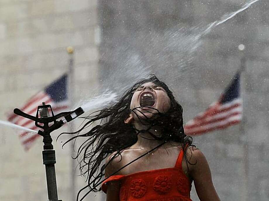 Patty Wesel, 8, from Marietta, Ga, jumps in the spray of a sprinkler on the National Mall in front of the Washington Monument in Washington Wednesday, July 7, 2010. The eastern U.S. cooked for another day as unrelenting heat promised to push thermometerspast 100 degrees. Photo: Alex Brandon, AP