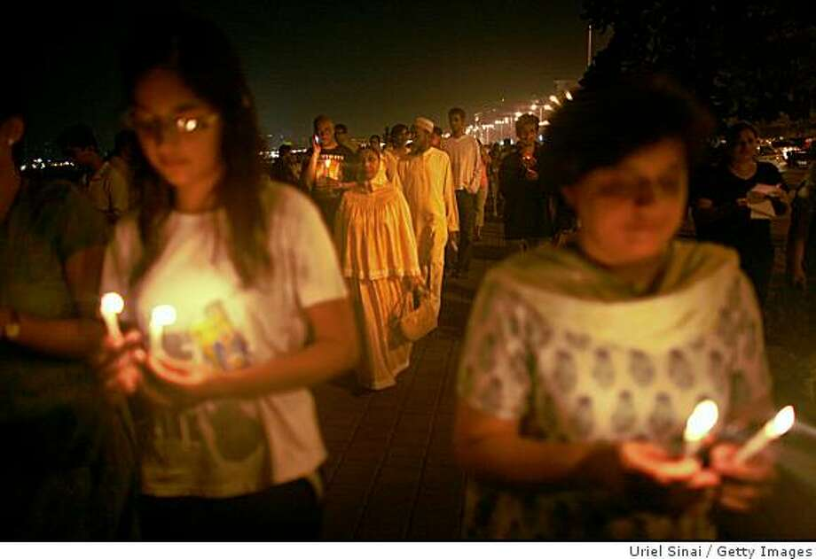 """MUMBAI (BOMBAY), INDIA - NOVEMBER 30: (ISRAEL OUT) Mumbai Residents attend a candlelit vigil in the street near The Oberoi Hotel following a demonstration against the recent terror attacks in the city on November 30, 2008 in Mumbai, India. Indian Home Minister Shivraj Patil today submitted his resignation claiming """"moral responsibility"""" following the Mumbai terror attacks. The city of Mumbai was rocked by multiple coordinated terrorist attacks that targeted locations popular with foreigners, late on November 26, killing nearly 200 people. (Photo by Uriel SinaiGetty Images) Photo: Uriel Sinai, Getty Images"""