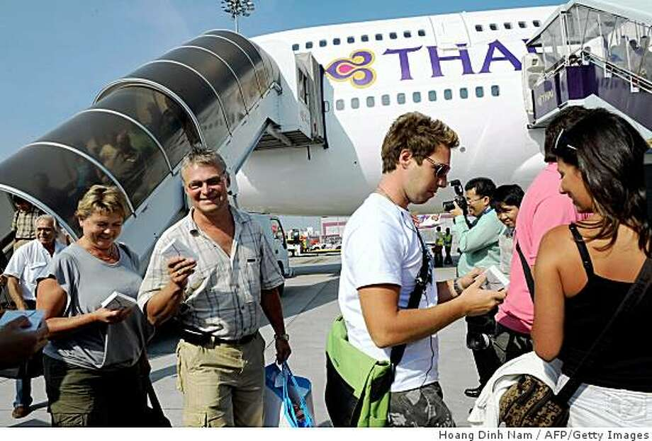 Passengers walk down from a Thai-Airways Boeing 747 at Suvarnabhumi international airport after making the first flight from the southern Thai town of Phuket in Bangkok on December 3, 2008.  Airlines gradually resumed international and domistic flights to and from the airport after protesters ended a blockade, with full operations expected on December 4, 2008.  AFP PHOTO/HOANG DINH Nam (Photo credit should read HOANG DINH NAM/AFP/Getty Images) Photo: Hoang Dinh Nam, AFP/Getty Images