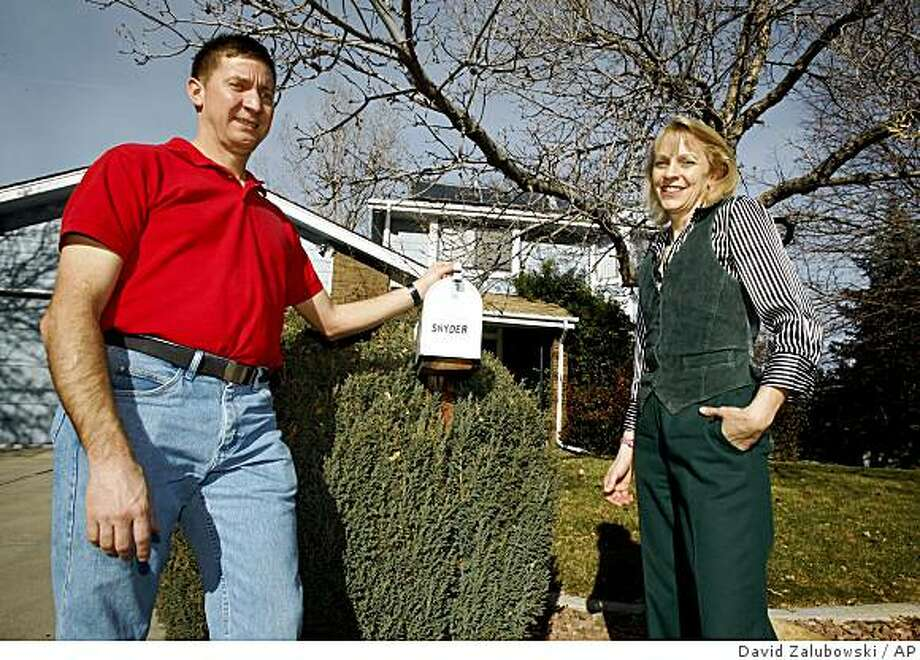 Nancy Partridge and her ex-husband, David Snyder, pose outside the home that they share in Westminster, Colo., on Tuesday, Dec. 2, 2008. The pair divorced in January after six years of marriage but when the house failed to sell and Partridge ran out of money to pay for an apartment and her half of the mortgage, she moved back in with Snyder in August. (AP Photo/David Zalubowski) Photo: David Zalubowski, AP