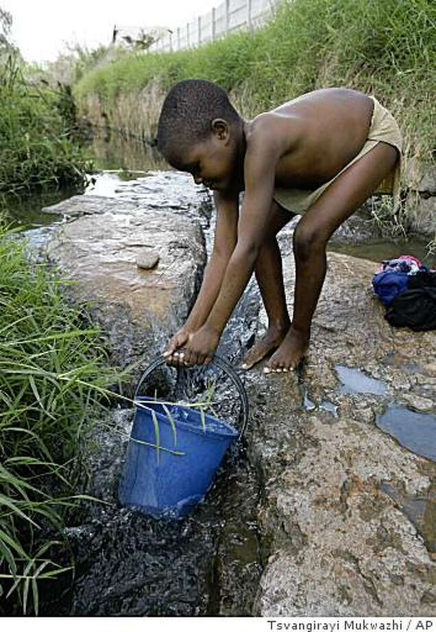 A young boy fetches water from a river after bathing in Harare, Zimbabwe Wednesday, December, 3, 2008. The United Nations is reporting that the death toll from the cholera epidemic in Zimbabwe has risen to 565, with 12,546 people infected. The government had been reporting 473 cholera deaths since August, and a total of 11,700 people infected as of Monday. The nationwide outbreak of the waterborne disease is blamed on collapsing water treatment plants and broken sewage pipes.(AP Photo/Tsvangirayi Mukwazhi) Photo: Tsvangirayi Mukwazhi, AP
