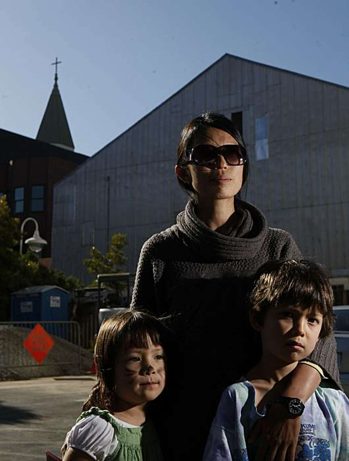 With steeple of St. Matthew's Lutheran Church looming in the background, a recently proposed site for a cell phone tower, Beverly Choe stands for portrait with her two children Anabel Harris, 4, and Ivan Harris, 6, in front of Children's Day School on Friday July 2, 2010 in San Francisco, Calif. Because of possible health concerns for her kids and other students in the area, Choe headed up a committee which ultimately resulted in cell compnay, T-Mobile, pulling out of the deal.