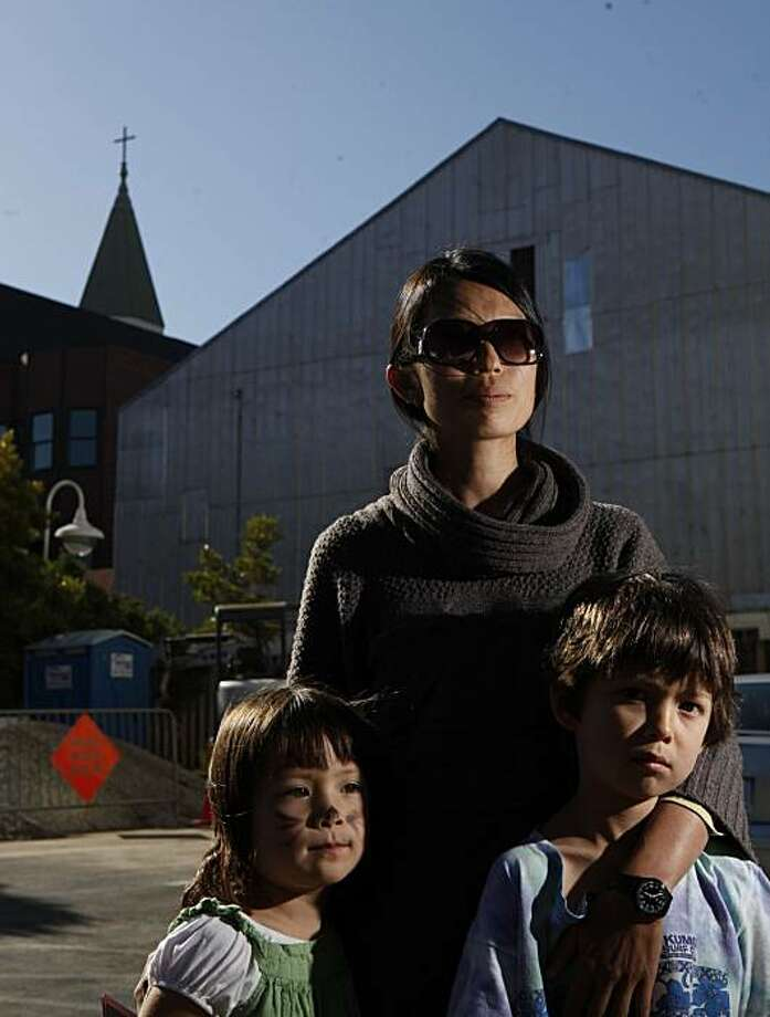 With steeple of St. Matthew's Lutheran Church looming in the background, a recently proposed site for a cell phone tower, Beverly Choe stands for portrait with her two children Anabel Harris, 4, and Ivan Harris, 6, in front of Children's Day School on Friday July 2, 2010 in San Francisco, Calif. Because of possible health concerns for her kids and other students in the area, Choe headed up a committee which ultimately resulted in cell compnay, T-Mobile, pulling out of the deal. Photo: Mike Kepka, The Chronicle