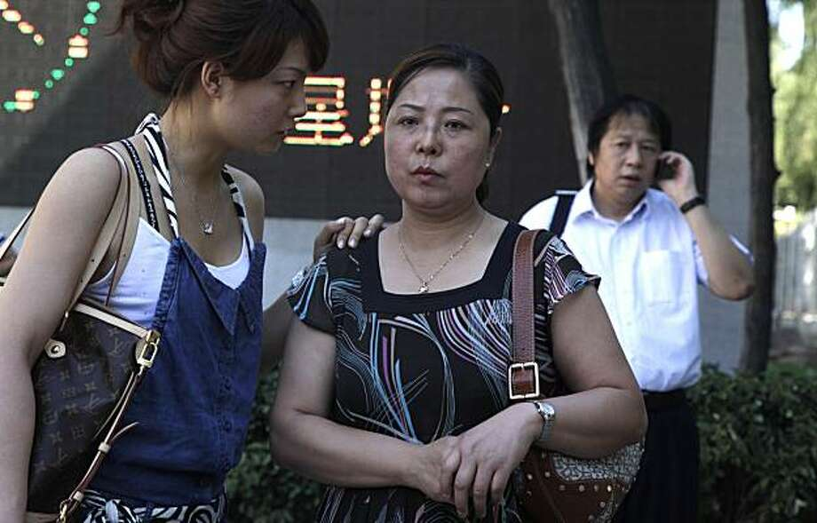 Xue Min, center, waits with her daughter Guo Jie for the trial of Xue's brother Xue Feng outside the Beijing No. 1 Intermediate People's Court where sentencing for Xue Feng was to take place in Beijing, China, Monday, July 5, 2010.  Xue Feng, an Americangeologist detained and tortured by China's state security agents over an oil industry database, was jailed for eight years Monday in a troubling example of China's rough justice system and the way the U.S. government handles cases against its citizens. The court  convicted Xue Feng of collecting intelligence for overseas and illegally providing state secrets. At right is Xue Feng's lawyer Tong Wei. Photo: Ng Han Guan, AP