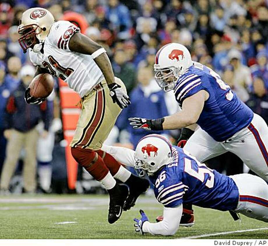 San Francisco 49ers' Frank Gore (21) runs under pressure from Buffalo Bills' Kyle Williams, right, and Keith Ellison (56) during the first half of the NFL football game at Ralph Wilson Stadium in Orchard Park, N.Y., Sunday, Nov. 30, 2008. (AP Photo/David Duprey) Photo: David Duprey, AP