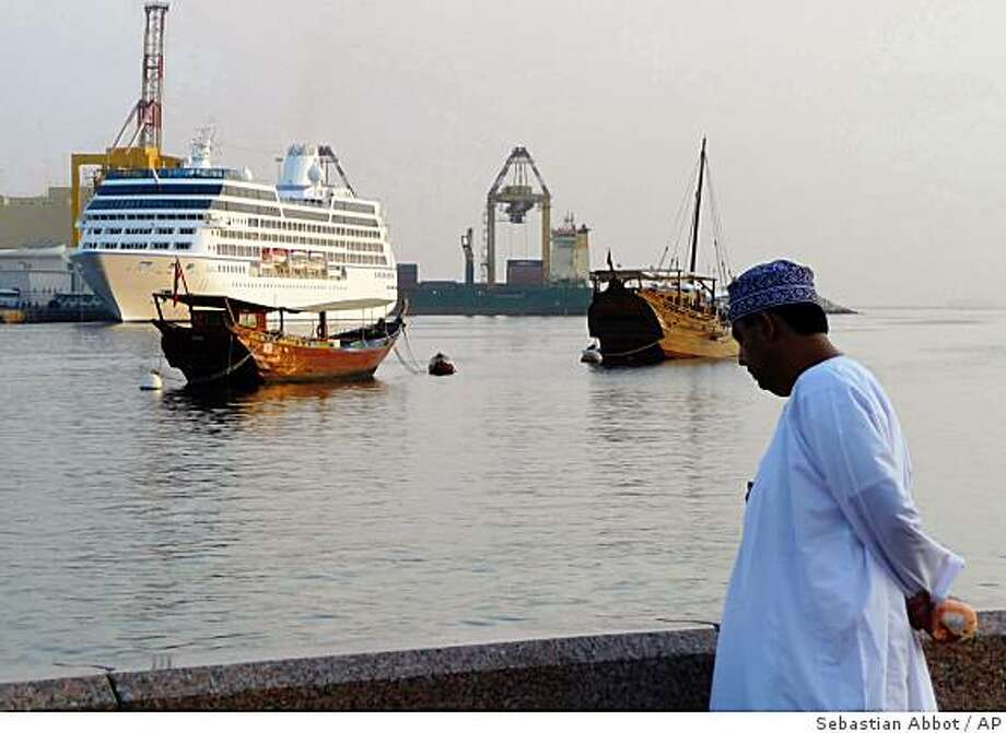 "An Omani citizen views the 600-foot long M/S Nautica, left, as it sails near traditional Omani boats and prepares for a daylong port stop in the Omani capital of Muscat Wednesday, Dec. 3, 2008. Passengers on a luxury cruise liner attacked by pirates in the dangerous waters between Yemen and Somalia said Wednesday they were surprised by the assailants' boldness and described hearing the ""pop, pop, pop"" of the pirates' rifles firing at the ship. Sunday's attack on the M/S Nautica in the Gulf of Aden was the latest evidence that pirates have grown more aggressive, viewing almost any ship on the water as a potential target.  (AP Photo/ Sebastian Abbot) Photo: Sebastian Abbot, AP"