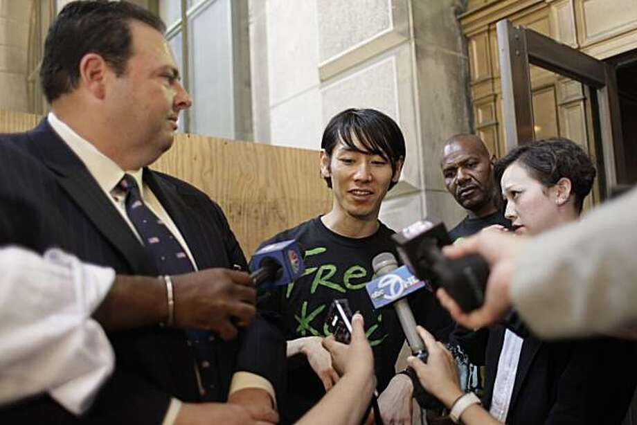 Six-time hot dog-eating contest champion Takeru Kobayashi, center, is joined by his attorney Mario D. Romano, left, and interpreter  Maggie James as he speaks to reporters after leaving Brooklyn Criminal Court, Monday, July 5, 2010, in New York. Kobayashiwas freed after a night in a New York jail  after he pleaded not guilty to charges of obstruction of governmental administration, resisting arrest, trespassing and disorderly conduct. Photo: Mary Altaffer, AP
