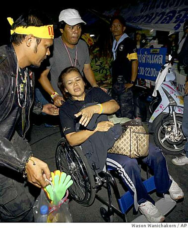 An injured anti-government protester is attended to by colleagues after an explosion during a protest at government house Sunday, Nov. 30, 2008 in Bangkok, Thailand. An emergency official says an explosion inside the Thai prime minister's besieged office compound has wounded 33 people. The protesters, who have occupied government house, the prime minister's compound, since August, upped the stakes this week by overrunning Bangkok's international and domestic airports and bringing them to a halt in their campaign to oust the government. (AP Photo/Wason Wanichakorn) Photo: Wason Wanichakorn, AP