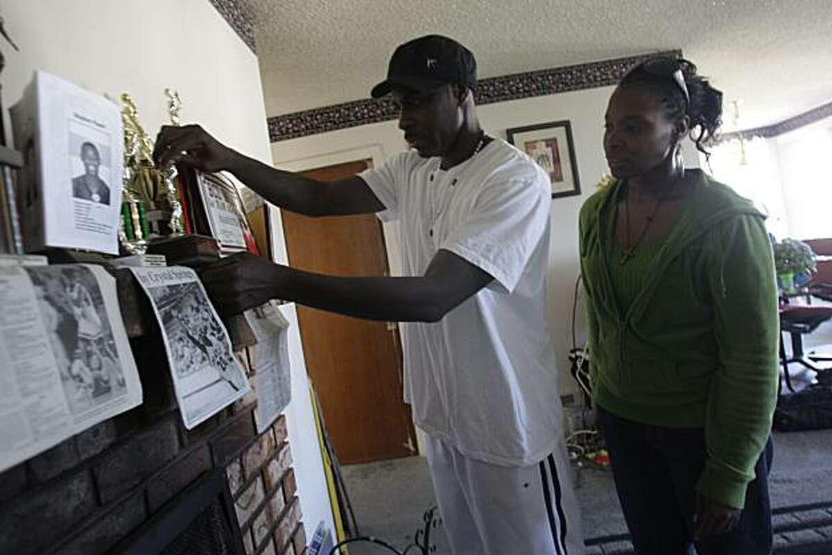 Stephen Powell, Sr. (left to right) and Stacey Powell, father and mother of Stephen Powell, Jr., arrange photos and newspaper articles of their son, Stephen Powell, Jr., who was killed Saturday night at a gay pride event, on the mantle at their home in San Francisco, Calif. on Wednesday June 30, 2010.