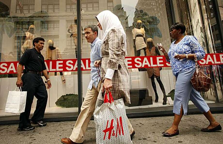 Shoppers leave an H&M clothing store, Thursday, July 8, 2010 in New York. Stores steepened discounts more than planned in June to help drive recession-scarred customers into the malls to buy summer merchandise. But shoppers spent cautiously amid escalating job worries, resulting in modest gains for many merchants. Photo: Mark Lennihan, AP