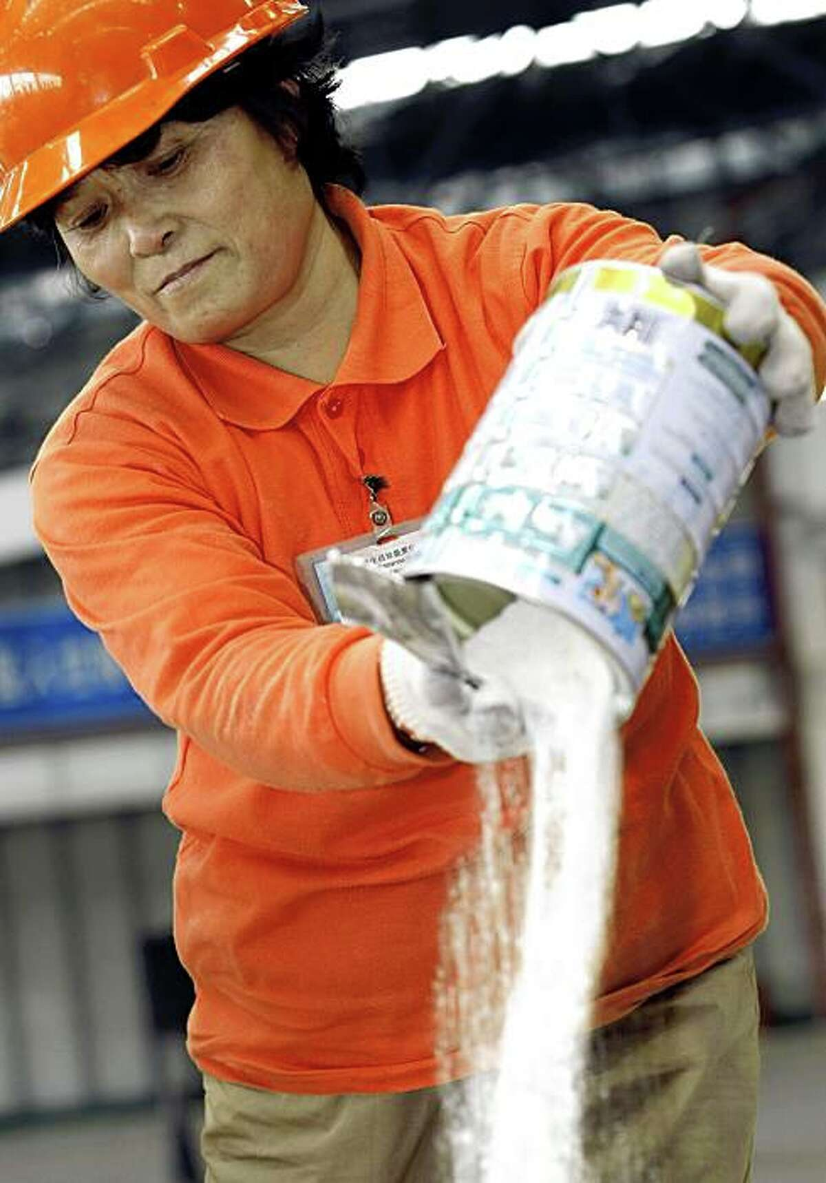A Chinese worker destroys a batch of tainted milk powder in Shanghai on November 14, 2008.