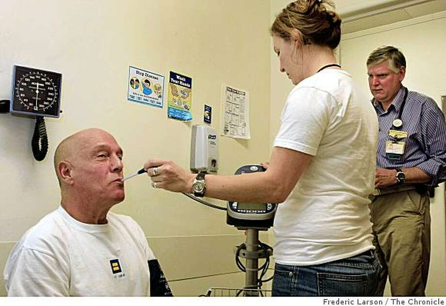 Richard Apodaca an AIDS out patient (sitting) gets a routine check up from  Katie Carlson, a medical assistance, while Dr. Dan Wlodarczyk (far right) looks on at the AIDS ward at San Francisco General Hospital on November 25, 2008. Photo: Frederic Larson, The Chronicle