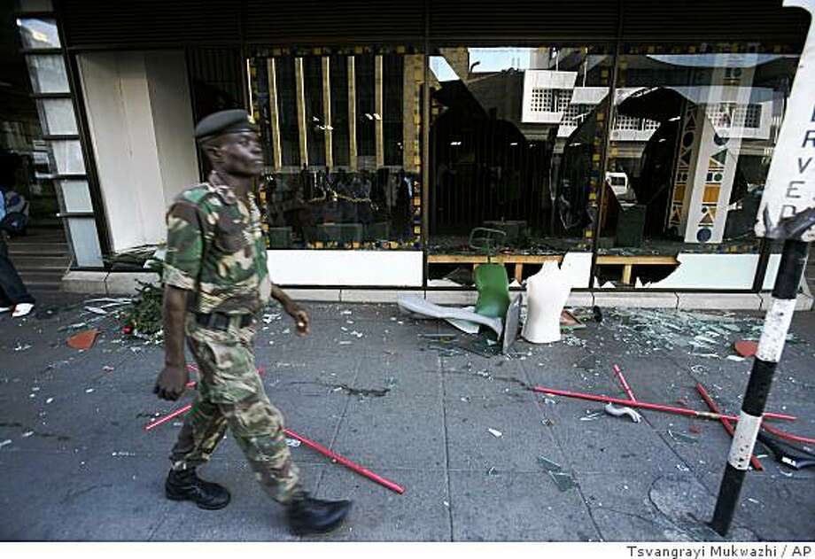A member of the Zimbabwe National Army walks past a looted shop in Harare, Monday, Dec. 1, 2008. Gunfire broke  out in downtown Harare when rampaging, unpaid soldiers attacked money changers and clashed with police.  (AP Photo/Tsvangirayi Mukwazhi) Photo: Tsvangrayi Mukwazhi, AP