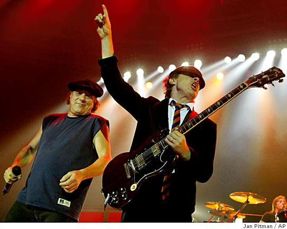 Brian Johnson, left, and Angus Young, right, of the Australian rock band AC/DC perform on stage during a concert of the band in Munich, southern Germany, on Tuesday, June 17, 2003. Photo: Jan Pitman, AP
