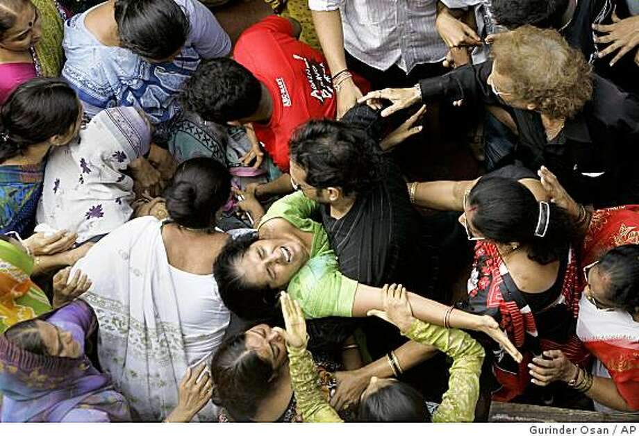 ** CORRECTS AGE OF VICTIM TO 25 ** Relatives and neighbors mourn as they attend the funeral of Haresh Gohil, 25, who was killed by gunmen near Chabad-Lubavitch center,also known as Nariman House in Mumbai, India, Saturday, Nov. 29, 2008. Indian commandos killed the last remaining gunmen holed up at a luxury Mumbai hotel Saturday, ending a 60-hour rampage through India's financial capital by suspected Islamic militants that rocked the nation. (AP Photo/Gurinder Osan) Photo: Gurinder Osan, AP
