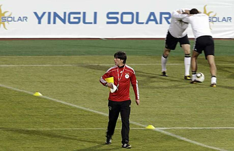 FILE - In this file photo taken Tuesday, June 22, 2010, Germany head coach Joachim Loew, front, walks over the pitch as German players stretch during a German team training session near a advertisement panel for Yingli Solar at the Super stadium in Atteridgeville near Pretoria, South Africa. China did not qualify for the World Cup, but the country is still making an appearance in South Africa. An ambitious Chinese solar company, the country's first World Cup sponsor, has placed advertising in all the stadiums in a bid to give its brand a worldwide boost. Yingli Green Energy Co.'s sponsorship deal allows it to show its logo of Yingli Solar, in Chinese and English, on electronic perimeter-boards at all 64 games of the World Cup. Photo: Gero Breloer, AP