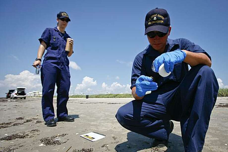 Marine Science Technician Third Class with the U.S. Coast Guard, Andrew Garcia, right, and Lt. Jamie Koppi analyze a tar ball specimen on Sunny Beach Tuesday, July 6, 2010, in Galveston, Texas. Most of the tar balls found were old solidified specimens. Further testing is needed to confirm whether fresh tar balls are associated with the Gulf Oil disaster. (AP Photo/Houston Chronicle, Michael Paulsen) MANDATORY CREDIT Photo: Michael Paulsen, Houston Chronicle