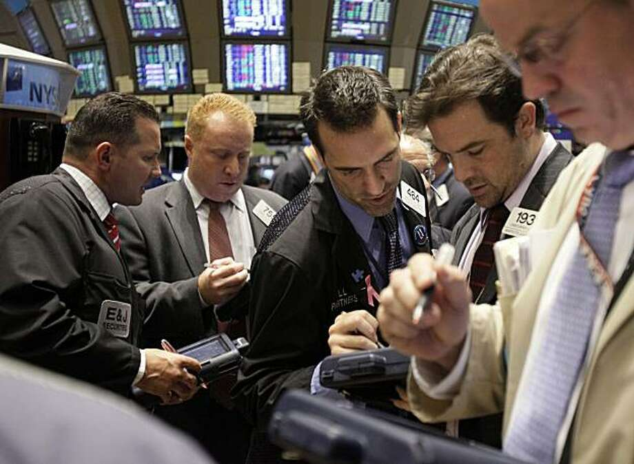 FILE - In this file photo taken June 25, 2010, traders work on the floor of the New York Stock Exchange. A day after the Dow Jones industrial average broke a seven-day losing streak, stocks are set to resume that slide. Photo: Richard Drew, AP