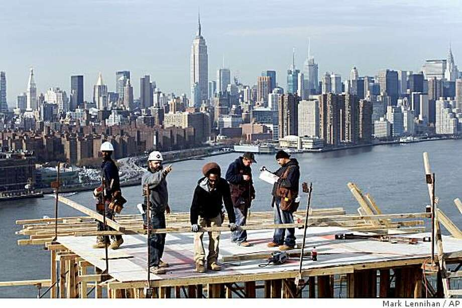 ** FILE ** In this Nov. 12, 2008 file photo, carpenters work on the roof of a 30-story condominium project in the Williamsburg section of New York. The Edge, built by Douglaston Development on the East River waterfront in Brooklyn and scheduled to open in the fall of 2009, will offer 565 apartments in two buildings. The Commerce Department on Monday, Dec. 1, 2008 reported construction spending fell by a larger-than-expected amount in October, another indication that problems facing the builders of homes, hotels and other projects are deepening and likely to persist. (AP Photo/Mark Lennihan) Photo: Mark Lennihan, AP