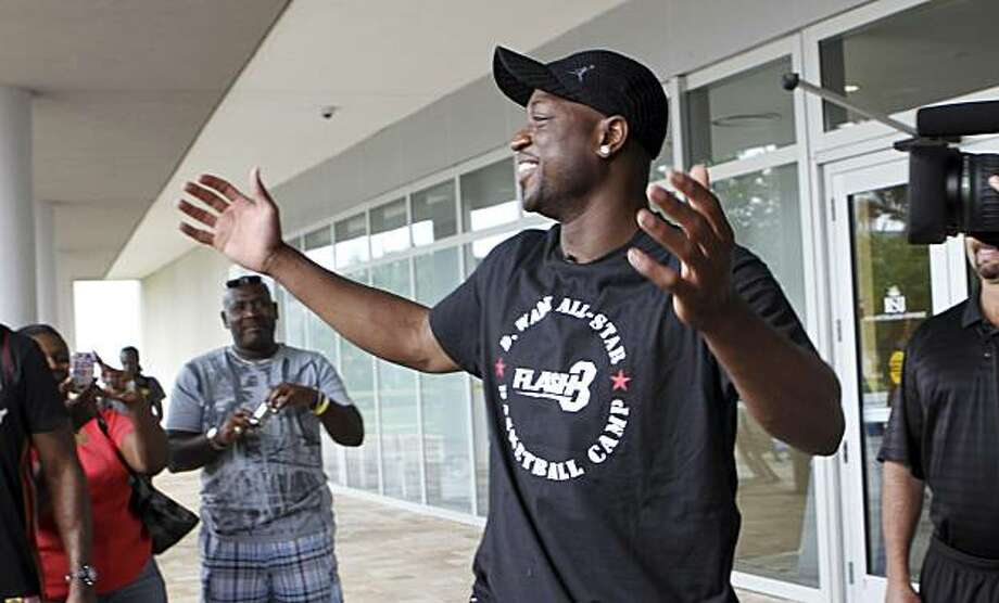 """Free-agent basketball  player Dwyane Wade raises his hands and smiles at Miami Heat employees as they chant """"We Want Wade!"""" at Nova Southeastern University in Davie, Fla., Tuesday, July 6, 2010. A free agent for the first time, Wade is torn between staying in Miami and playing elsewhere, most likely Chicago. He's had at least two conversations with the Bulls since free agency began last week, plus has met with the New York Knicks and New Jersey Nets. Photo: Alan Diaz, AP"""