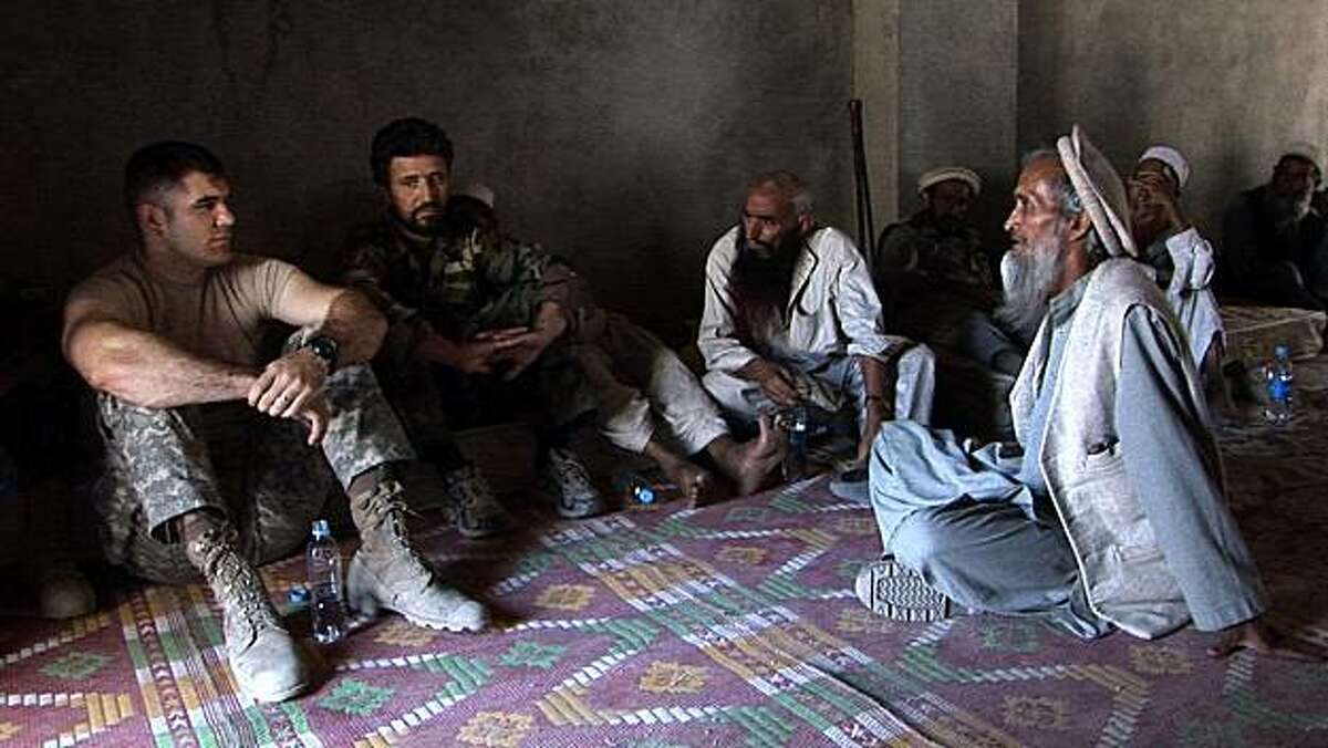 """In this 2008 film publicity image released by Outpost Films, Capt. Dan Kearney of Battle Company, 173rd US Airborne, left, meets with local Afghan elders in the Korengal Valley, Kunar Province, Afghanistan in a scene from the documentary """"Restrepo."""""""