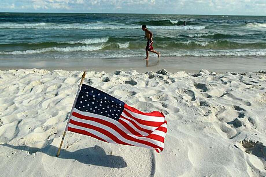 GULF SHORES, AL - JULY 04:  An American flag is stuck in the sand along a beach which was not as busy as last year as people stayed away due to the threat of contamination from the Deepwater Horizon oil spill in the Gulf of Mexico on July 4, 2010 in GulfShores,Alabama. The oil spill may have a huge negative economic impact on gulf coast businesses during what should be a busy 4th of July. Millions of gallons of oil have spilled into the Gulf since the April 20 explosion on the drilling platform. Photo: Joe Raedle, Getty Images