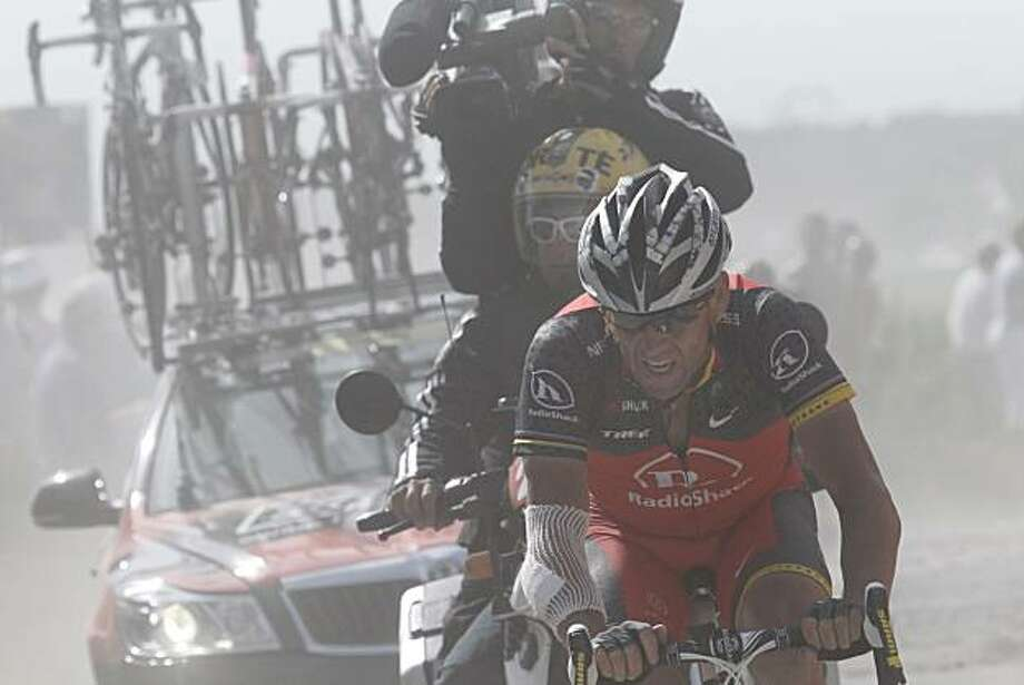 Lance Armstrong of the US rides in a cloud of dust on a cobblestone section during the third stage of the Tour de France cycling race over 213 kilometers (132.4 miles) with start in Wanze, Belgium and finish in Arenberg, France, Tuesday July 6, 2010. Photo: Joel Saget, AP