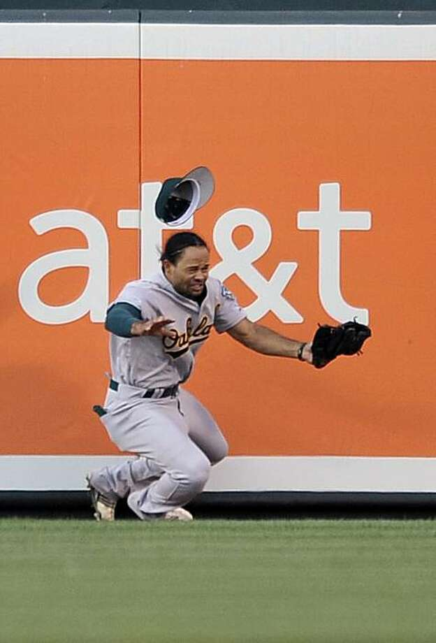 Oakland Athletics center fielder Coco Crisp makes a leaping catch and hits the wall on a ball hit by Baltimore Orioles' Corey Patterson in the second inning of a baseball game Wednesday, June 30, 2010, in Baltimore. Catcher interference was called on the play. (AP Photo/Gail Burton). Photo: Gail Burton, AP