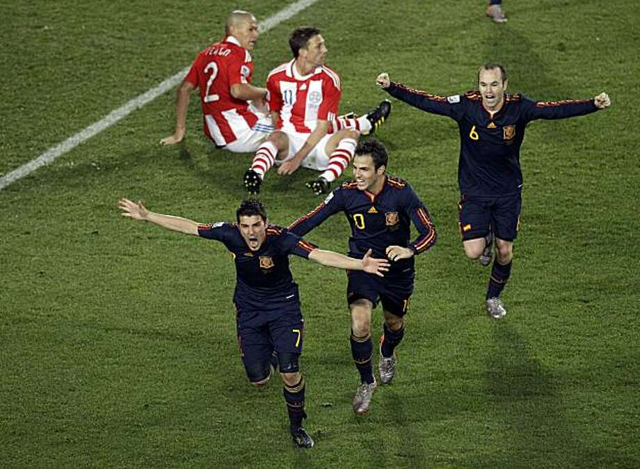 Spain's David Villa, bottom left, celebrates with Spain's Cesc Fabregas and Spain's Andres Iniesta, right, after scoring during the World Cup quarterfinal soccer match between Paraguay and Spain at Ellis Park Stadium in Johannesburg, South Africa, Saturday, July 3, 2010. Photo: Themba Hadebe, AP
