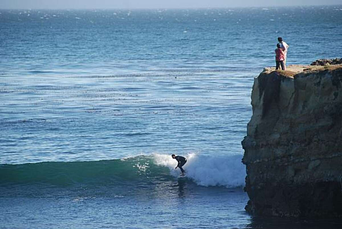 A couple watches the action from a cliff above Steamer Lane.