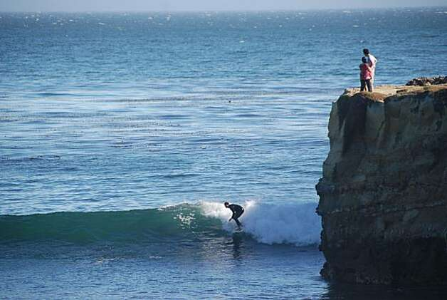 A couple watches the action from a cliff above Steamer Lane. Photo: Jill K. Robinson, Special To The Chronicle