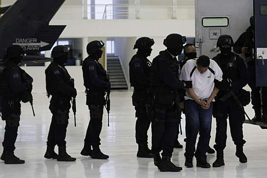"Jesus Ernesto Chavez, known as ""El Camello"", is led by federal police officers during a presentation to the press, in Mexico City, Friday, July 2, 2010. According to the federal police Chavez ordered the March 13 attack that killed a U.S. consulate employee and her husband as they drove in the violent border city. Photo: Carlos Jasso, AP"