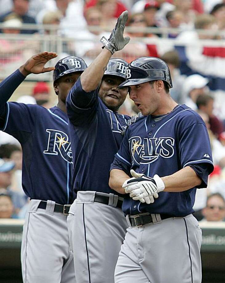 Tampa Bay Rays designated hitter Matt Joyce, right, is congratulated by teammates Willy Aybar, center, and B.J. Upton after hitting a grand slam in the eighth inning off Minnesota Twins pitcher Alex Burnett during their baseball game Saturday, July 3, 2010, in Minneapolis. The Rays defeated the Twins 8-6. Photo: Andy King, AP
