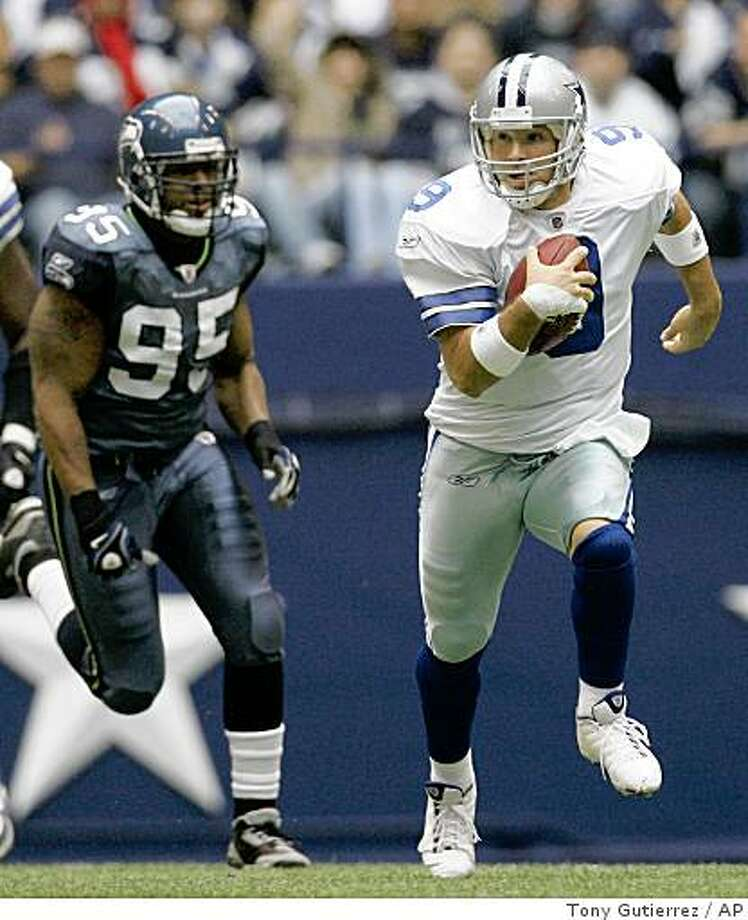Dallas Cowboys quarterback Tony Romo, right, scrambles past Seattle Seahawks defensive end Lawrence Jackson for a first down during the first quarter NFL football game on Thanksgiving Day, Thursday, Nov. 27, 2008, in Irving, Texas. Dallas won 34-9. (AP Photo/Tony Gutierrez) Photo: Tony Gutierrez, AP