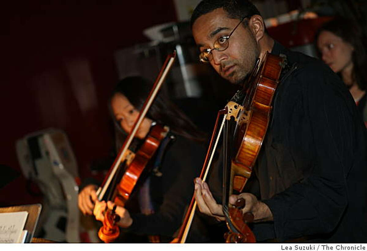 Charith Premawardhana (foreground) and Jenn Chang (background left) perform at Classical Revolution at The Revolution Cafe on Sunday, November 9, 2008 in San Francisco, Calif.