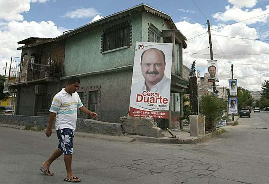 A man walks next to a poster with political propaganda of Chihuahua State Governor candidate, Cesar Duarte from the Institutional Revolutionary Party (PRI) on July 2, 2010, in Ciudad Juarez, Mexico. Sunday's elections in nearly half of Mexico's states areexpected to serve as an unofficial referendum on President Felipe Calderon's clampdown on drug violence that is gripping the country. Photo: Jesus Alcazar, AFP/Getty Images