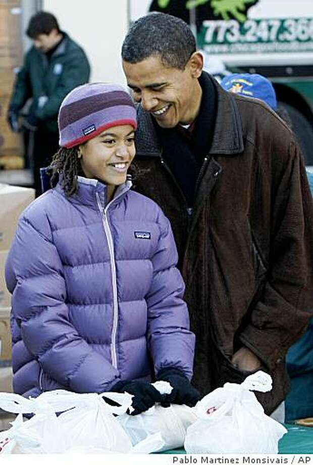 President-elect Barack Obama, right, with his daughter Malia, 10, wait to greet people at a food bank at  St. Columbanus Catholic Church on the South Side of Chicago, Wednesday, Nov. 26, 2008. (AP Photo/Pablo Martinez Monsivais) Photo: Pablo Martinez Monsivais, AP