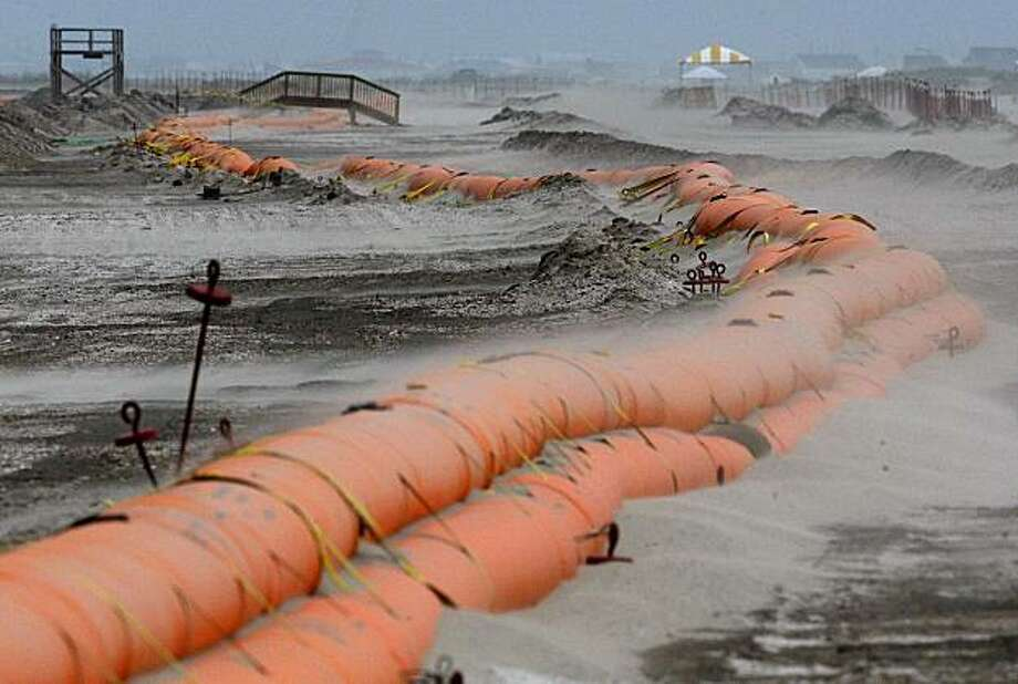 Sand blows across a tiger dam on a beach as the outer edges of Tropical Storm Alex approach the Louisiana coast in Grand Isle, La., Tuesday, June 29, 2010. The dam is expected to protect the island's beaches from oil that washes ashore from April's Deepwater Horizon oil rig explosion and spill in the Gulf of Mexico. Photo: Patrick Semansky, Associated Press