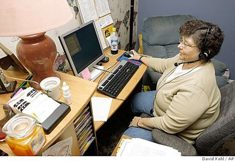 Sharon Castor, an at-home agent for Convergys Corp. of Cincinnati, works at her desk at her Florence, Ky. home, Tuesday, June 3, 2008.  The economic crisis and volatile gas prices are fueling movement of call-center work from sprawling offices with hundreds of people working at once into one-person operations in homes across the nation.  (AP Photo/David Kohl) Photo: David Kohl, AP