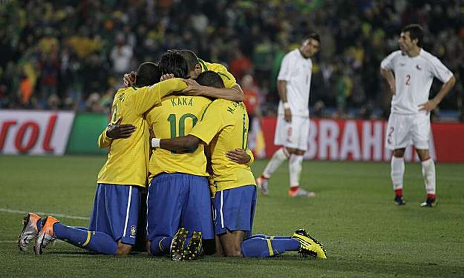 Brazil's Robinho, hidden, celebrates with teammates after scoring the third goal during the World Cup round of 16 soccer match between Brazil and Chile at Ellis Park Stadium in Johannesburg, South Africa, Monday, June 28, 2010. Photo: Matt Dunham, AP