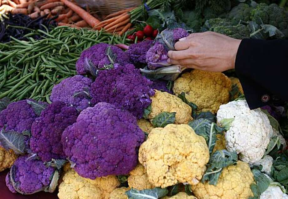 A shopper chooses from a variety of cauliflower from the Specialty Produce stand at the Heart of the City farmers market at UN Plaza in San Francisco, Calif., on Wednesday, July 8, 2009. Vendors at the civic center market have long been accepting food stamp tokens from customers. A plan proposed by Mayor Newsom will require all farmers markets to do the same citywide. Photo: Paul Chinn, The Chronicle