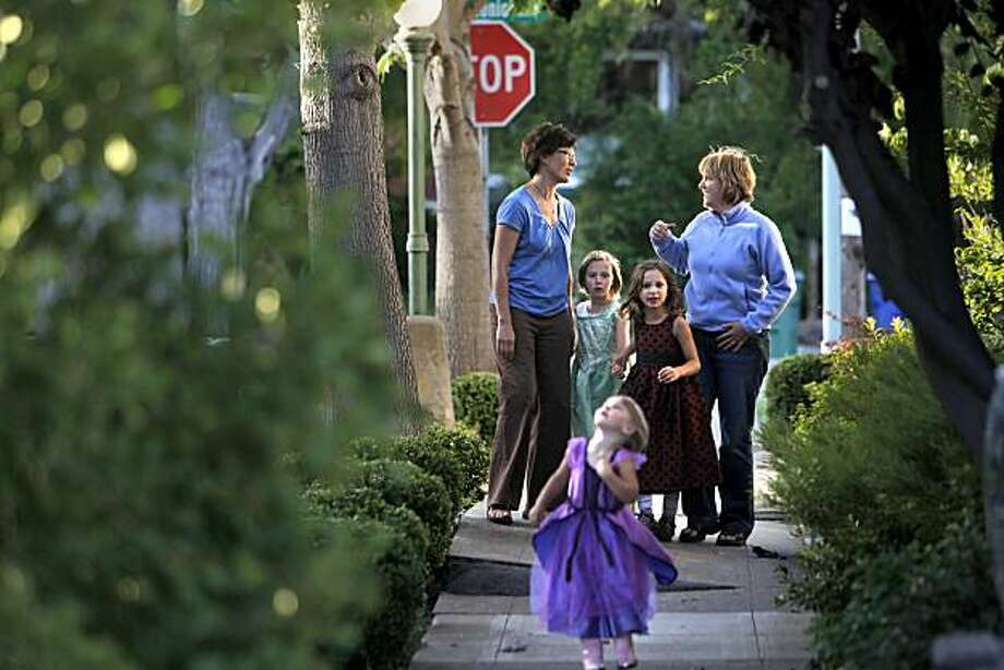 Jenny Johnson, left, talks with her neighbor, Amy Pernick, right, as her daughter's Zoey and Amelia Ericson, (green and purple dresses) and Sydney Olken, (red dress) play nearby on Wednesday, June 30, 2010, in Alameda, Calif. Johnson knocked on doors for Measure E, a parcel tax that failed, and schools will experience major cuts because of it. But supporters of Measure E are hopeful that they can regroup and pass a future tax to save the schools. Photo: Carlos Avila Gonzalez, The Chronicle