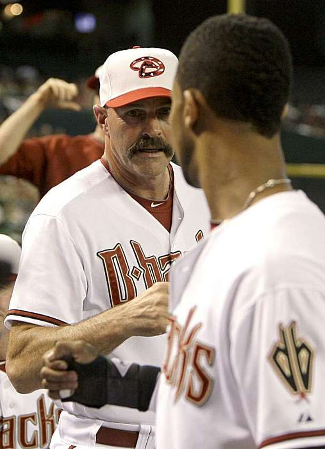 Arizona Diamondbacks new interim manager Kirk Gibson, left, gives Chris Young a fist pump after Young scored against the Los Angeles Dodgers in the first inning of a baseball game Friday, July 2, 2010, in Phoenix. Photo: Ross D. Franklin, AP