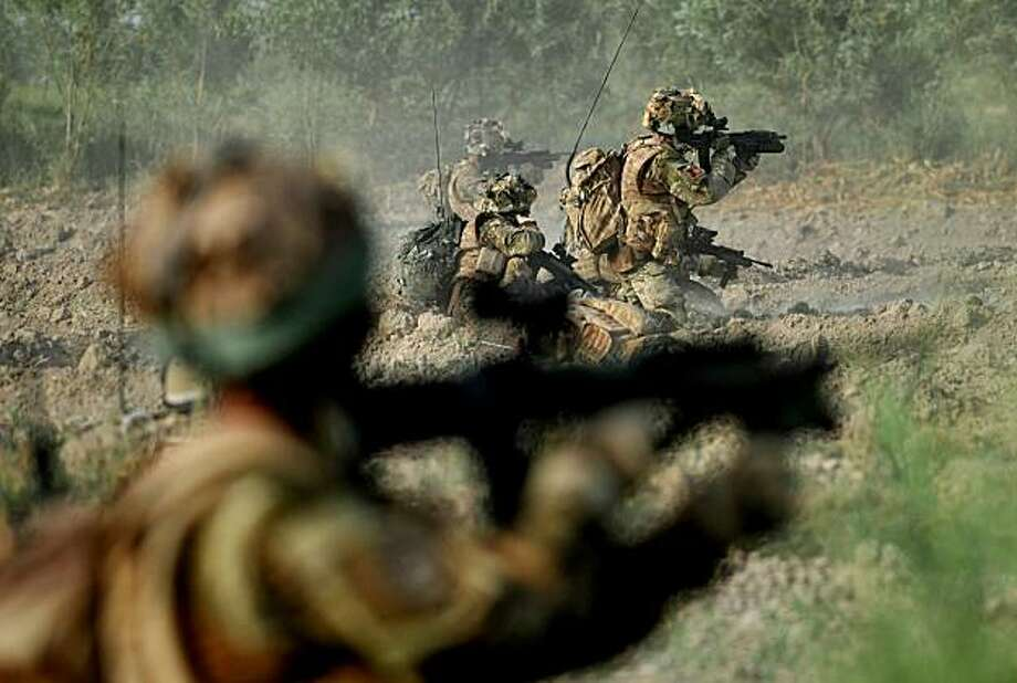 Major Josh Bowman (R), commanding officer of A Company of 1st Battalion Royal Gurkha Rifles, returns fire during a contact with insurgents on a field outside a village in Nahr e Saraj, in Helmand, on June 26, 2010 during the 17-hour Operation Kapcha Door.Britain has around 9,500 troops in Afghanistan and is the second biggest contributor of forces to ISAF after the United States. Photo: Bay Ismoyo, AFP/Getty Images